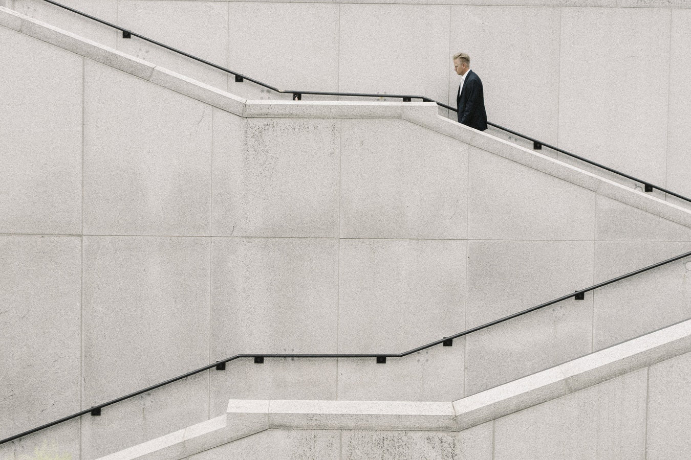 crisis management, businessman walking up concrete stairs