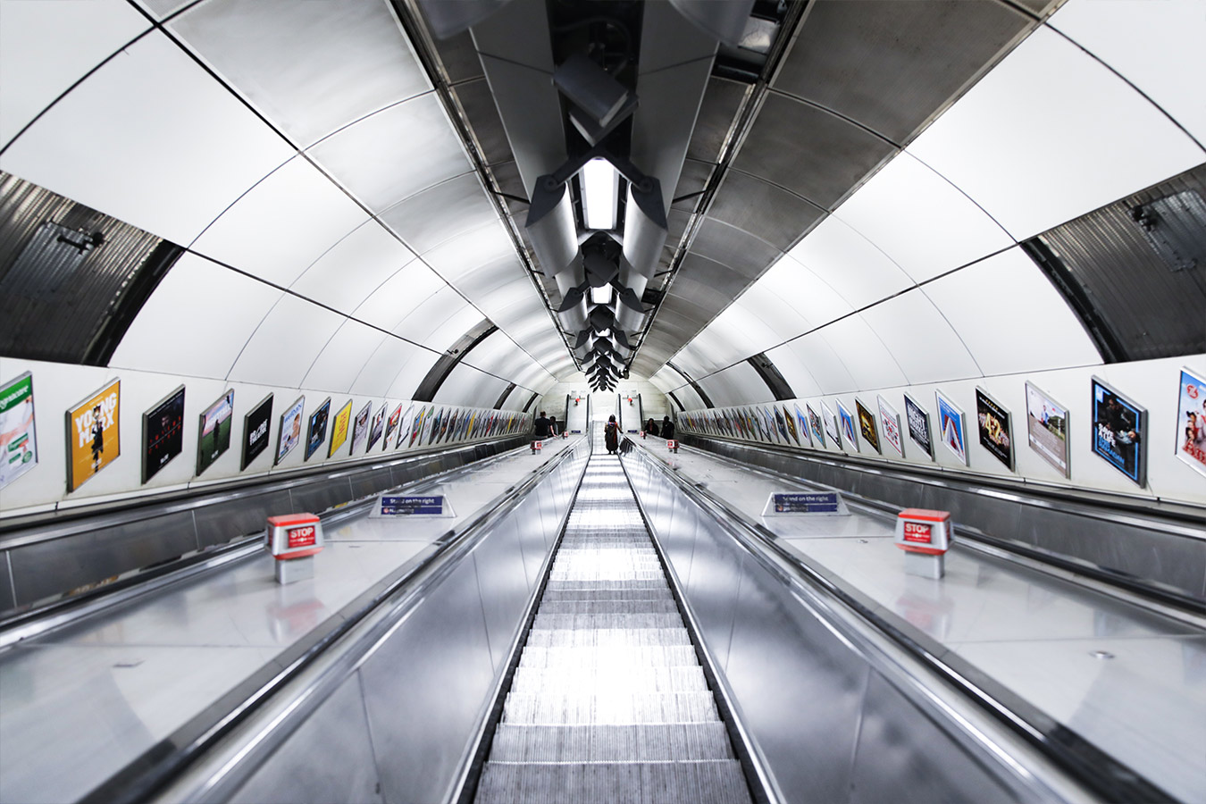 escalator tunnel lined with advertising campaign posters